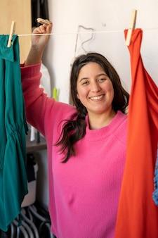 Photo verticale d'une jeune femme avec un pull rose et des cheveux longs qui traînent des vêtements