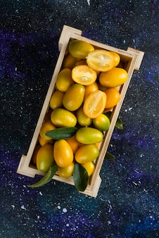 Photo verticale de kumquats biologiques dans une boîte en bois sur une surface bleue