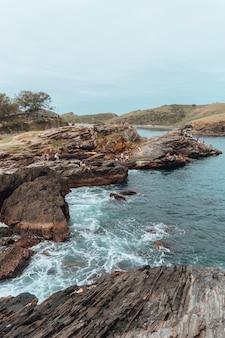 Photo verticale de la mer entourée de rochers et de verdure à rio de janeiro au brésil