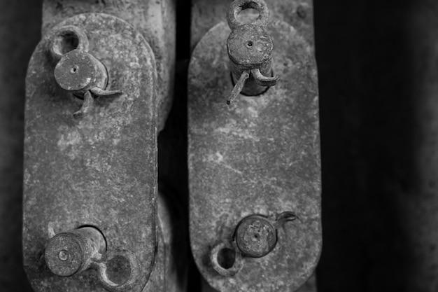 Photo verticale non saturée de vieilles pièces de fer rouillé liées entre elles concept vintage et antique