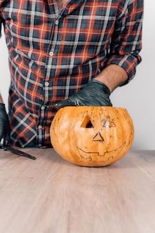 Une photo verticale d'une personne portant des gants et sculpter une citrouille pour halloween