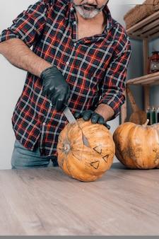 Une photo verticale d'une personne portant des gants tout en coupant une citrouille pour halloween