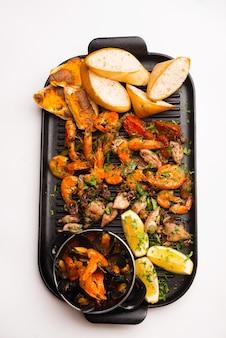 Photo verticale d'un plateau avec des fruits de mer préparés.