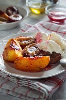 Photo verticale de prunes et de pêches au four avec crème glacée et miel et cannelle