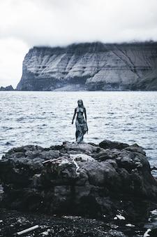 Une photo verticale d'une statue féminine près de la mer