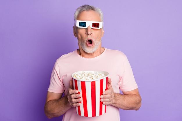 Photo d'un vieil homme étonné tenir un seau en papier pop corn bouche ouverte porter des lunettes 3d t-shirt rose fond de couleur violet isolé