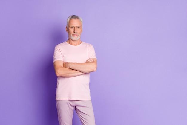 Photo d'un vieil homme sûr de lui, visage calme, mains jointes, porter un pantalon rose t-shirt fond de couleur violet isolé