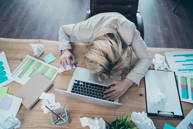 Photo de vue à angle élevé au-dessus de la tête de femme d'affaires allongé sur le bureau à l'intérieur
