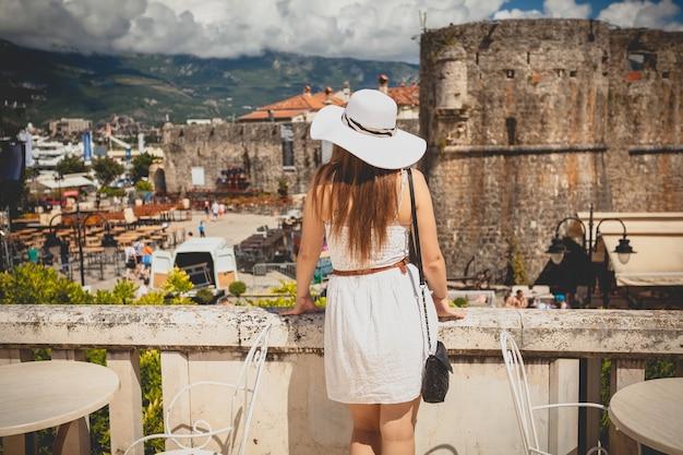 Photo vue arrière d'une belle femme portant un chapeau regardant la vieille ville