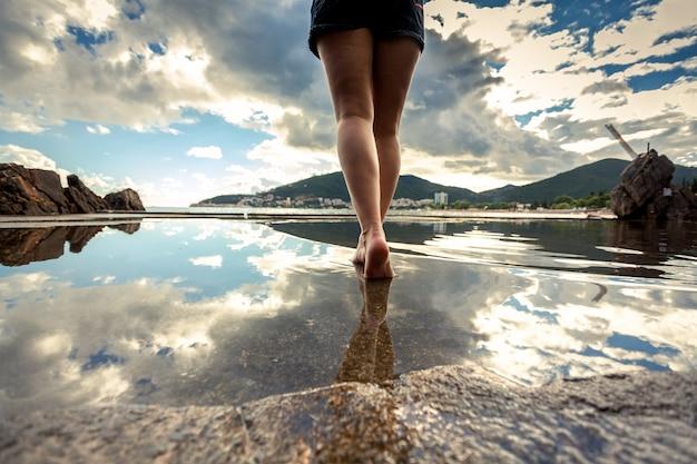 Photo vue arrière de belles jambes féminines minces marchant sur la surface de l'eau avec un ciel réfléchissant