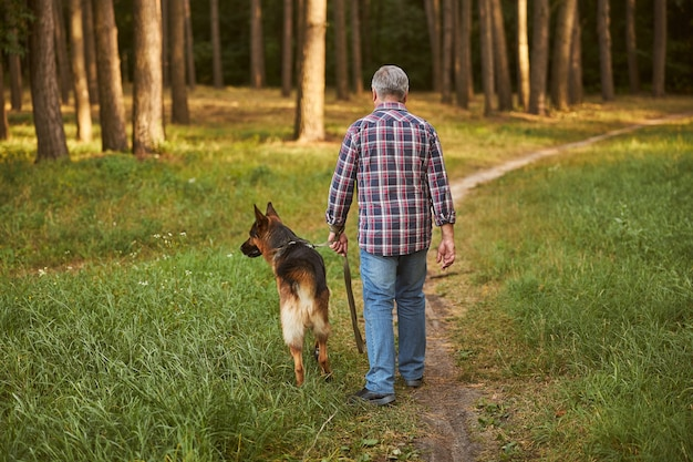 Photo vue arrière d'un homme vieillissant et de son chien marchant dans la forêt