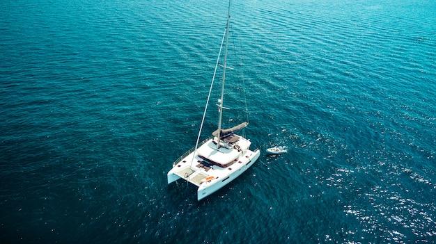 Photo vue de dessus de drone aérien d'un yacht de luxe avec un bateau en caoutchouc blanc. phuket. thaïlande.