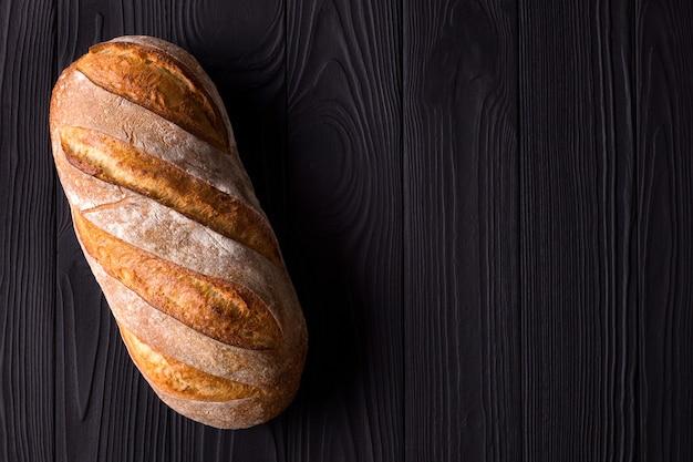 Photo vue de dessus du pain frais sur table en bois noir.