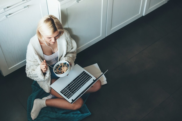 Photo vue de dessus d'une femme de race blanche aux cheveux blonds et écouteurs assis dans la cuisine sur le sol et à l'aide d'un ordinateur portable de manger des céréales