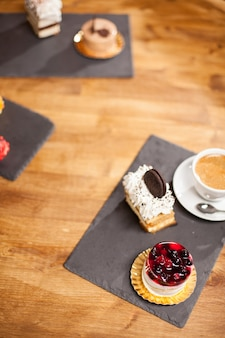 Photo vue de dessus d'un gâteau avec un délicieux biscuit près de différents mini-gâteaux sur une table en bois dans un café. délicieux gâteau avec des fruits savoureux sur le dessus et de la crème au café.