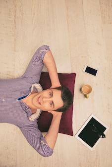 Photo vue de dessus de l'homme allongé sur le sol avec tasse, téléphone, lunettes et tablette