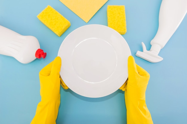 Photo vue de dessus des mains dans des gants en caoutchouc jaune tenant une assiette blanche avec une éponge et des détergents dans des bouteilles sur fond bleu isolé.