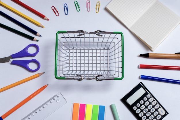 Photo vue de dessus d'un petit panier au centre et fournitures de bureau colorées, isolé sur une surface blanche