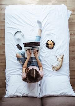 Photo vue de dessus pleine longueur d'une jeune femme brune dans des vêtements décontractés pendant qu'elle travaille avec un ordinateur portable au lit. fille heureuse étudie avec un chien à la maison