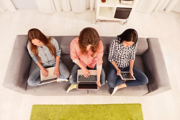 Photo vue de dessus de trois filles travaillant sur ordinateur portable et tablette numérique