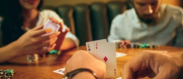 Photo vue latérale d'amis assis à table en bois. amis s'amusant tout en jouant au jeu de société.