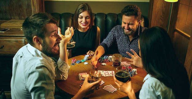 Photo vue latérale d'amis masculins et féminins assis à une table en bois. hommes et femmes jouant au jeu de cartes. mains avec gros plan d'alcool.