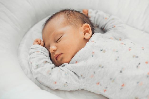 Photo vue supérieure d'un bébé nouveau-né de race blanche dormant dans des vêtements blancs à la maison