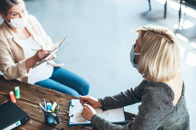 Photo vue supérieure d'une femme senior de race blanche avec masque médical travaillant avec un client à l'aide de certains livres et crayons