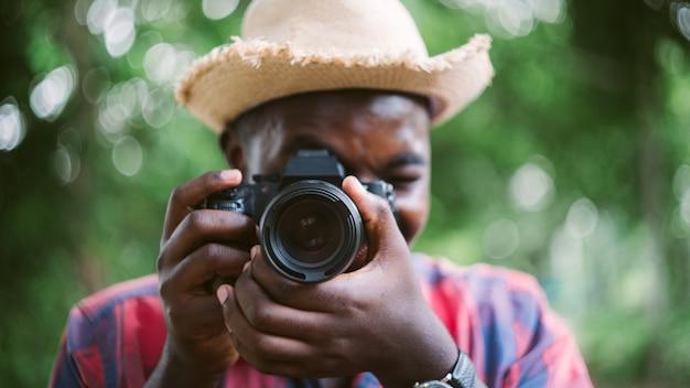 Un photographe africain prend des photos avec l'appareil photo numérique