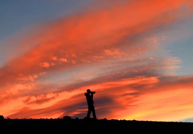 Photographe avec appareil photo en face du ciel rouge