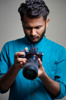 Photographe avec appareil photo sur fond blanc.