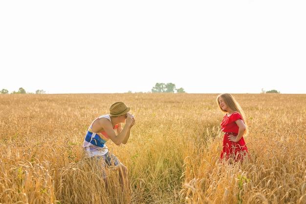 Photographe avec appareil photo prenant une photo d'une belle jeune femme sur le terrain.
