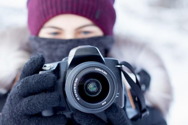 Un photographe avec un appareil photo professionnel prend des photos en hiver par temps froid