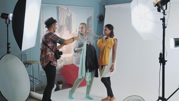 Photographe avec assistant choisissant des vêtements pour la prise de vue du modèle