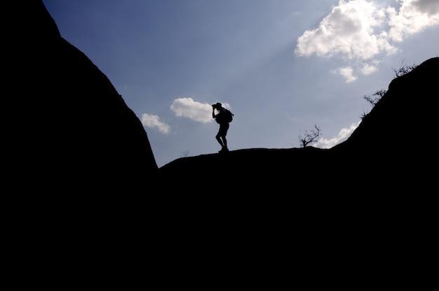 Un photographe au sommet d'une montagne se découpe sur un ciel de nuages