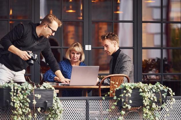 Photographe avec caméra parle aux gens. un jeune homme en vêtements formels a une discussion d'affaires avec une vieille femme au café.