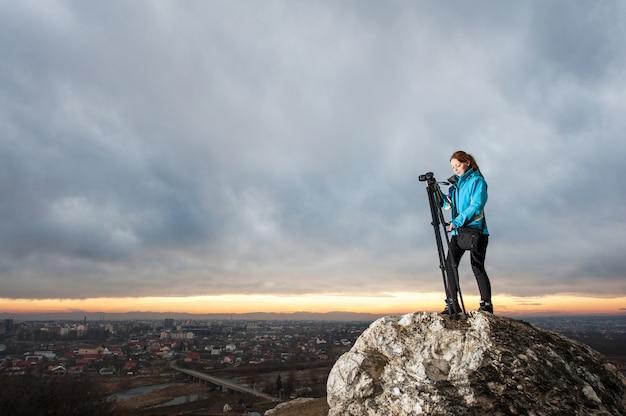 Photographe avec caméra sur trépied sur le gros rocher