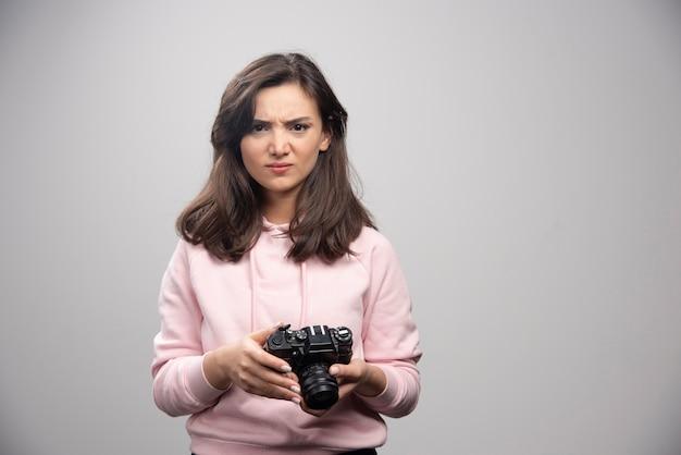 Photographe en colère tenant la caméra sur un mur gris.
