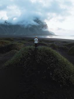 Photographe sur une colline verdoyante de la péninsule de stokksnes dans le sud-est de l'islande