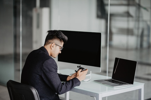 Photographe confiant. enthousiaste jeune homme tenant un appareil photo numérique et souriant alors qu'il était assis sur son lieu de travail