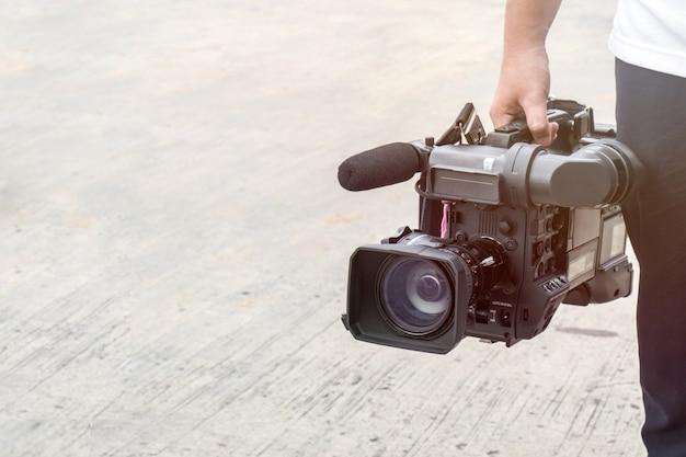 Photographe couvrant un événement en plein air avec une caméra vidéo