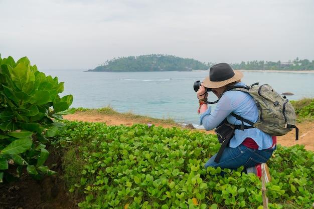 Le photographe dans un chapeau et avec un sac à dos prend une photo.