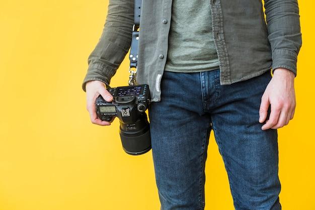 Photographe debout avec caméra