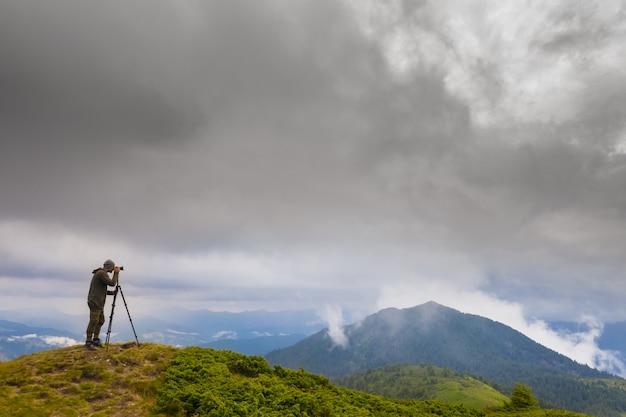 Le photographe debout sur la montagne avec des nuages pluvieux