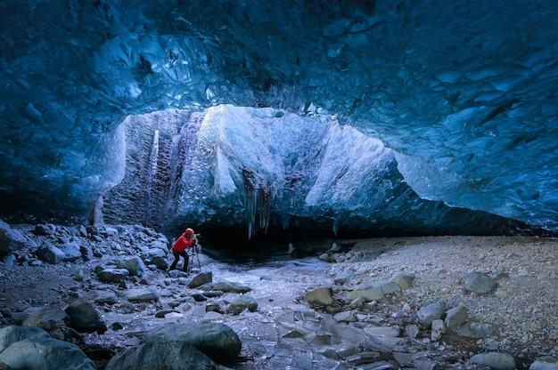 Photographe debout sous terre à l'intérieur d'un glacier, climat spécifique, parc national de vatnajokull, nature étonnante de skaftafell, entrée d'une grotte de glace, islande