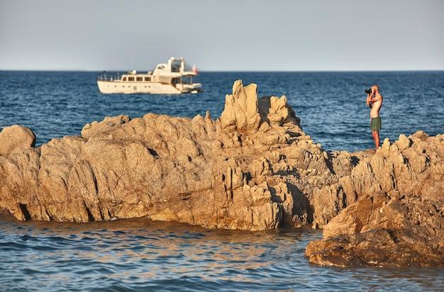 Photographe désireux de photographier un paysage naturel debout au sommet d'une falaise