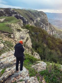 Photographe de drone commençant un drone au lever du soleil sur une falaise dans les montagnes. vue verticale.
