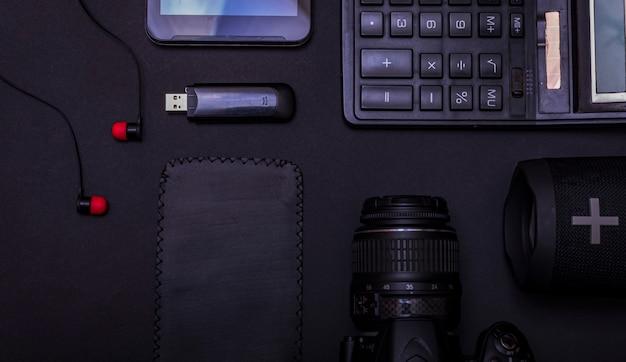Photographe d'espace de travail vue de dessus avec appareil photo numérique, calculatrice, clé usb et accessoire sur fond de tableau noir avec espace de copie.