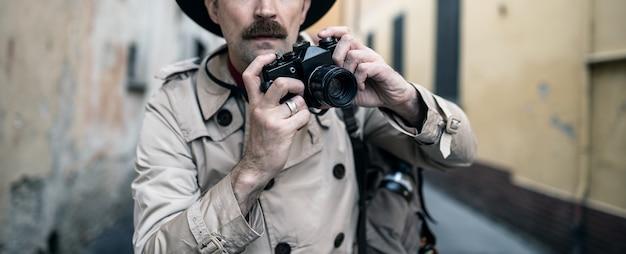 Photographe espion ou paparazzo, homme utilisant un appareil photo dans une rue de la ville