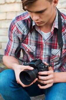 Photographe examinant la caméra. beau jeune homme examinant son appareil photo numérique alors qu'il était assis à l'extérieur